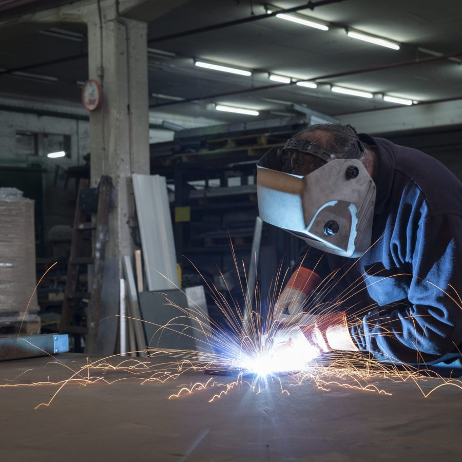 Single worker welding working in a steel factory with sparks flyig